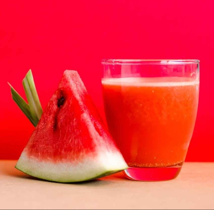watermelon shake filled glass cup beside sliced watermelon fruit on brown surface